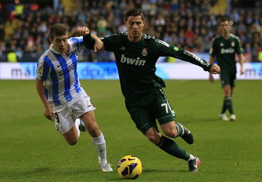 Bintang Real Madrid, Cristiano Ronaldo saat berduel dengan pemain Malaga, Francisco Portillo, Minggu (23/12) dinihari WITA.
